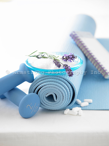 Yoga mat rolled up, with 2lb weights, dish of lavendar and salt, and vitamin tablets. All objects are white, blue and purple.