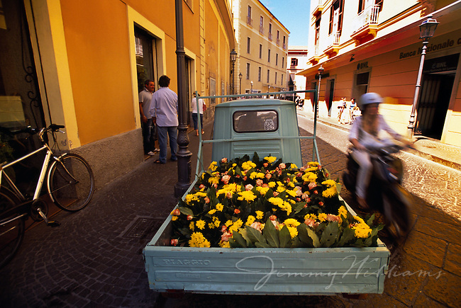 An old truck carrying flowers drives through a busy Sorento street