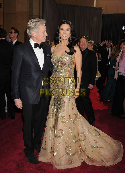 Michael Douglas & Catherine Zeta-Jones (wearing Zuhair Murad).85th Annual Academy Awards held at the Dolby Theatre at Hollywood & Highland Center, Hollywood, California, USA..February 24th, 2013.oscars full length silver gold beige tulle metallic dress sequins sequined beads beaded black trousers blue suit jacket white shirt bow tie married husband wife profile  .CAP/ROT/TM.©Tony Michaels/Roth Stock/Capital Pictures