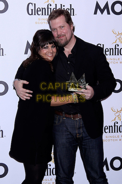 Rumer (Sarah Joyce) & John Grant.The Glenfiddich MOJO Honours List award ceremony, the Brewery, Chiswell St., London, England..July 21st, 2011.half length black dress cape top singer songwriter fringe bangs hair award trophy winner hug embrace suit jacket jeans denim beard facial hair .CAP/COA/CC.©CC/COA/Capital .