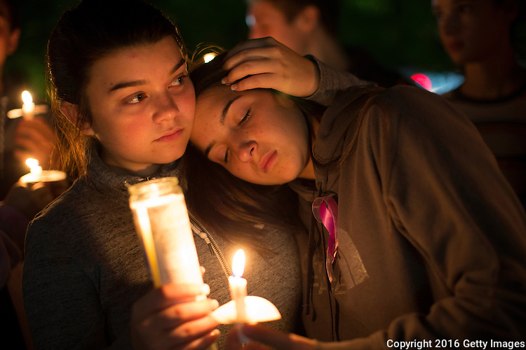 BURLINGTON, WA - SEPTEMBER 26: Tatum Sprouse (left), 17, and Rainah Douglas, 16, both from Mount Vernon, Washington, participate in a candlelight vigil along Burlington Boulevard on September 26, 2016 in Burlington, Washington. Five people were killed by a gunman several nights ago at thre Cascade Mall. One of those killed was a classmate of theirs at school. The suspect, Arcan Cetin, 20, a resident of Oak Harbor, Washington, was arraigned today. (Photo by Karen Ducey/Getty Images)
