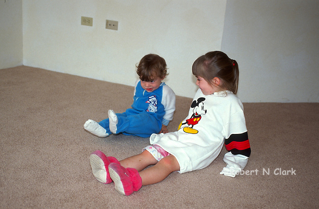 Big sister watching little one-year old brother raise his leg on carpet