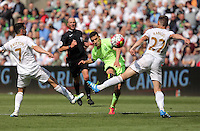 Jesus Navas of Manchester City (C) takes a shot off tarket, he is marked by Leon Britton (L) and Angel Rangel of Swansea City (R) during the Swansea City FC v Manchester City Premier League game at the Liberty Stadium, Swansea, Wales, UK, Sunday 15 May 2016