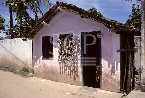Bahia, Brazil. A little girl peers out from a pink fisherman's hut; fish hung out to dry and sell.