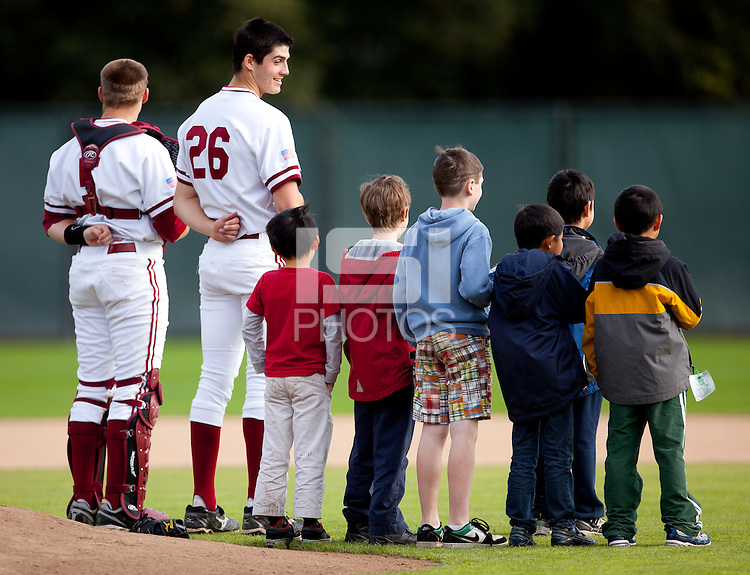 STANFORD, CA - March 25, 2011: Zach Jones and Mark Appel of Stanford baseball stand at attention with kids during the singing of the National Anthem before Stanford's game against Long Beach State at Sunken Diamond. Stanford lost 6-3.