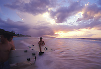 Surfers at sunset holding boards at Ehukai Beach, North Shore of Oahu, Hawaii