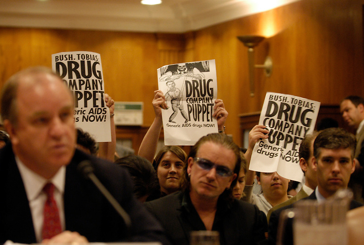Demonstrators from HealthGap hold up signs promoting generic Aids medication during Randall Tobias, global HIV/AIDS coordinator testimony at a Senate Appropriations AIDS Programs and Research Foreign Operations Subcommittee hearing on FY2005 appropriations for HIV/AIDS programs and research. Bono, founder, DATA (Debt, AIDS, Trade, Africa) and singer of U2 sits behind him.....