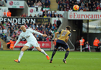 (L-R) Jonjo Shelvey of Swansea heads the ball over Mesut Ozil of Arsenal during the Barclays Premier League match between Swansea City and Arsenal at the Liberty Stadium, Swansea on October 31st 2015