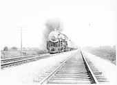 An almost head-on view of Santa Fe Pacific #3404 approaching with a passenger train.<br /> AT&amp;SF  near Chicago, IL  1931
