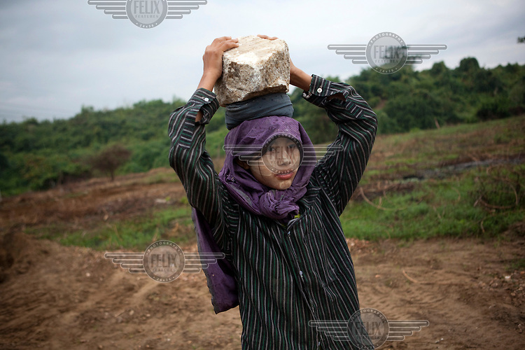 A 14 year old girl carries rocks as she works on a construction site in Naypyitaw, the new capital of Burma (Myanmar) since November 2005.