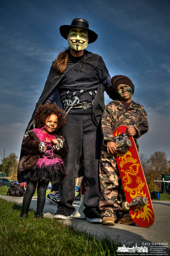 Man wearing Guy Fawlkes costume with children at Halloween skateboarding event at Westerville Skate Park.