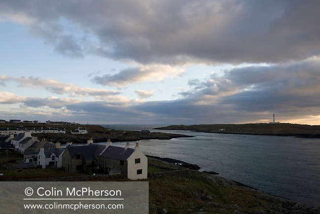 Dusk descending on a winter's evening over the Rinns of Islay lighthouse and the village of Portnahaven on the inner Hebridean island of Islay on Scotland's west coast. The island is famous for its whisky which is distilled there but is also an important site for migrating birds and wildlife. Islay has a total area of just over 600 square kilometres (239 square miles) and a population of around 3500.