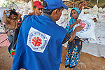 A Rohingya woman receives a bag of food during an aid distribution by Caritas in the Mainerghona Refugee Camp near Cox's Bazar, Bangladesh, on October 27, 2017. Since August more than 600,000 Rohingya have fled government-sanctioned violence in Myanmar for safety in Bangladesh.