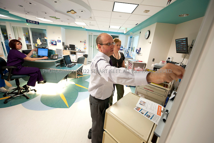 6/29/2010--Seattle, WA, USA...Dr. Howard Jeffries, the Medical Director of CPI at Seattle Children's uses s a white board at the entrance of the Cardiac Intensive Care Unit that shows a map of the rooms with patient names and gives a quick status of how full the unit is and how sick the patients are. Stick-on stars indicate a patient on a ventilator, while an orange circle shows a patient who needs to be in isolation...The board is one example of continuous process improvement (CPI), a practice which has touched just about every department of Seattle Children's Hospital.  Using the new system, the Seattle Children's has saved $200 million in building costs by using the facilities they have more efficiently...©2010 Stuart Isett. All rights reserved.
