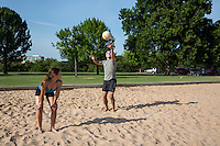 Fit attractive male athlete serves the ball during a volleyball match at Zilker Park, Austin, Texas.