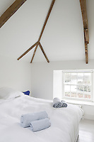 The guest bedroom also makes a feature of the roof beams and is simply furnished with a divan bed