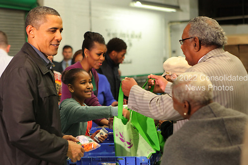 United States President Barack Obama, Sasha Obama, and First Lady Michelle Obama fill bags with produce at the Capital Area Food Bank in North East Washington DC on November 23, 2011.  r.Credit: Dennis Brack / Pool via CNP