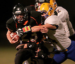 HOWARD, SD - NOVEMBER 8:  Luke Loudenburg #23 from Howard drags a pair of defenders with him including Gavin Doering #44 from Alcester Hudson in the first half of their Class 9A Semifinal game Saturday night in Howard. (Photo by Dave Eggen/Inertia)