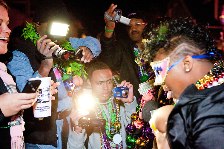 A woman exposes herself to get beads while many onlookers film her on Bourbon Street during Mardi Gras in New Orleans on February 15, 2010.