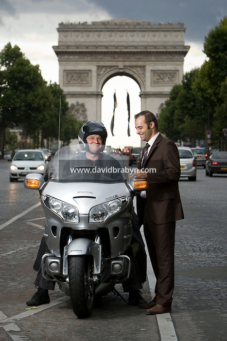 Motocab driver George Meunier (L) riding a Motocab Honda Goldwing 1800 and Japauto Honda dealer Director Jose Alves talk near the Arc de Triomphe in Paris, France, 21 August 2008.