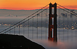 San Francisco Golden Gate Bridge during the early morning hour at sunrise with the city in the background that is surrounded by fog.