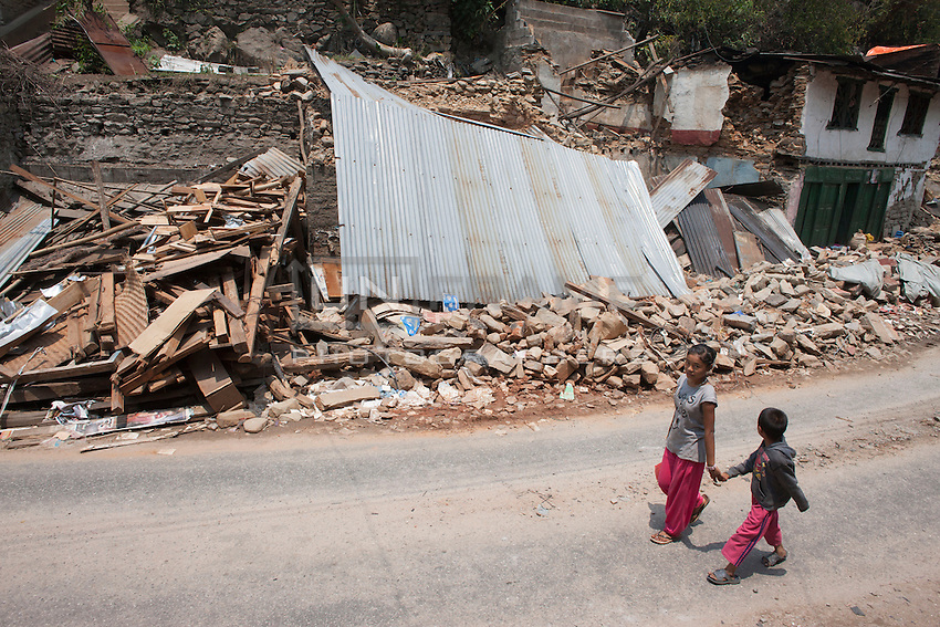 Children walk in front of collapsed houses at Shila Porbot, outskirts of Kathmandu, Nepal. May 8, 2015