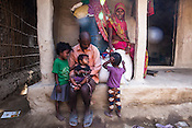 28 year old Asha Devi poses for a portrait with her husband and three of her daughters - Radha (left), Sharda (centre) and Rukmini (right) in their house in Saptari, Nepal. <br /> Asha Devi got married when she was 14. She got pregnant after 6 months of her marriage. Her first child survived for 6 days, she woke up next to a dead baby. She was pregnant two months later. Asha Devi's 2nd daughter survived for 9 months and later died due to prolonged fever. 3 months after her daughter died, Asha was pregnant again and within w months, she had spontaneous abortion. She was pregnant with Radha Kumari mandal who was acutely malnourished. Radha was admitted when she was 36 months old on October, 20th 2013. MUAC - 110 mm, Weight - 7 kg, Height - 75 cm. Radha was discharged on Dec 6, 2013 - her MUAC at the time of discharge was 128mm, Weight 8.8kg and height- 75.5 cm. She consumed 100 sachets of RUTF and gained 5gm/day while on the programme. <br /> Rukmini, her second daughter was born a year after Radha was born. Rukmini was severely malnourished too. She was admitted on Feb 16th, 2014. Her MUAC was 119mm, weight - 11 kg, and height - 96 cm. Her third daughter Sharda is severely malnourished. Sharda is under RUTF.  <br /> Asha Devi is pregnant for the 7th time and is 6 months pregnant.