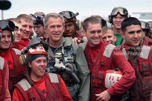 """United States President George W. Bush posses with Sailors for a photo on the flight deck after a successful trap aboard USS Abraham Lincoln (CVN 72) in a S-3B Viking assigned to the Blue Wolves of Sea Control Squadron Three Five (VS-35) designated """"NAVY 1"""" on May 1, 2003.   President Bush is the first sitting President to trap aboard an aircraft carrier at sea. The President is conducting a visit aboard ship to meet with the Sailors and will address the Nation as Lincoln prepares to return from a 10-month deployment to the Arabian Gulf in support of Operation Iraqi Freedom. <br /> Credit: United States Navy via CNP"""