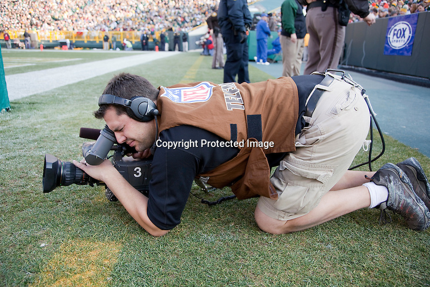 Fox Network Photographer Jeff Peil shoots video during the Green Bay Packers NFL football game against the San Francisco 49ers at Lambeau Field on November 22, 2009 in Green Bay, Wisconsin. The Packers won 30-24. (AP Photo/David Stluka)