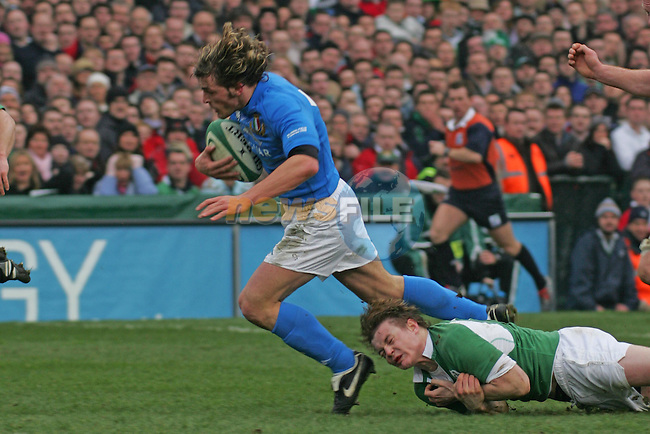 Dublin Ireland, the Opening match of the RBS Six nations between Ireland and Italy, Italys no 12 Micro Bergamasco escapes from the clutches of Ireland no 13  Brian O'Driscoll during the match in Lansdopwne road, Dublin. 4/2/06.Photo AFP/NEWSFILE/FRAN CAFFREY..(Photo credit should read AFP PHOTO/FRAN CAFFREY/NEWSFILE)...This Picture has been sent you under the condtions enclosed by:.Newsfile Ltd..the Studio,.Millmount Abbey,.Drogheda,.Co Meath..Ireland..Tel: +353(0)41-9871240.Fax: +353(0)41-9871260.GSM: +353(0)86-2500958.email: pictures@newsfile.ie.www.newsfile.ie.FTP: 193.120.102.198..This picture is from Fran Caffrey@newsfile.ie
