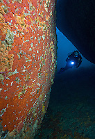 RS0953-D. scuba diver (model released) navigates between giant boulders 60 feet below the surface in Governor Island Marine Nature Reserve off Bicheno, along the east coast of Tasmania. The rock wall to the left is covered in red Southern Jewel Anemones (Corynactis australis). Tasmania, Australia, Pacific Ocean.<br /> Photo Copyright &copy; Brandon Cole. All rights reserved worldwide.  www.brandoncole.com