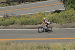 Caucasian male biking uphill on Lookout Mountain Road west of Denver, Colorado. .  John leads private photo tours in Boulder and throughout Colorado. Year-round.