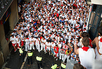 People waits the beginning of the last San Fermin Festival´s running of the bulls, on July 14, 2013, in Pamplona, Basque Country. On each day of the eight San Fermin festival days six bulls are released at 8:00 a.m. (0600 GMT) to run from their corral through the narrow, cobbled streets of the old navarre town over an 850-meter (yard) course. Ahead of them are the runners, who try to stay close to the bulls without falling over or being gored. (Ander Gillenea / Bostok Photo)
