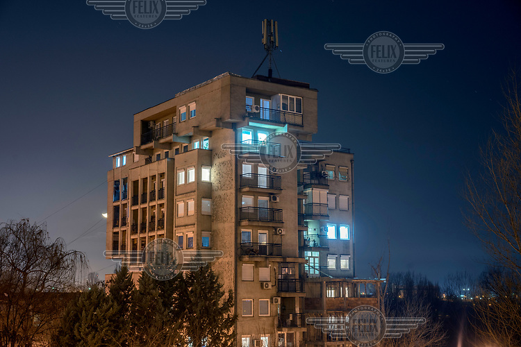 A residential block, its apartments illuminated at night.