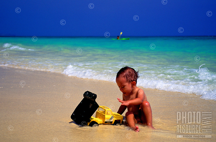 A small toddler boy plays with a dump truck on the sand at Lanikai Beach on the windward side of   Oahu.