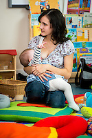 "A mother breastfeeding her baby at a drop-in breastfeeding support centre while talking to another mother.<br /> <br /> Image from the ""We Do It In Public"" documentary photography project collection: <br />  www.breastfeedinginpublic.co.uk<br /> <br /> Dorset, England, UK<br /> 17/04/2013"