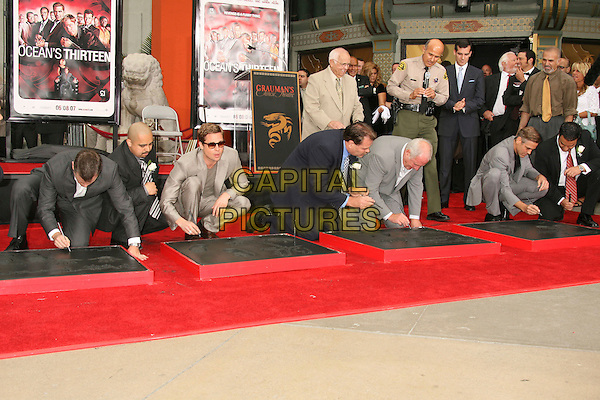 "MATT DAMON, BRAD PITT, JERRY WEINTRAUB & GEORGE CLOONEY.""Ocean's Thirteen"" Handprint and Footprint Ceremony held  at Grauman's Chinese Theatre, Hollywood, California, USA..June 5th, 2007.full length grey gray suit beige kneeling crouching bending over signing name .CAP/ADM/RE.©Russ Elliot/AdMedia/Capital Pictures"