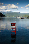 Life guard seat at high tide. Deep Cove Bay with clouds above the mountains over Mount Seymour provincial park. Deep Cove, Burrard Inlet, Vancouver, British Columbia, Canada.