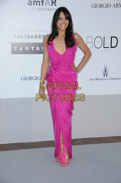 MICHELLE RODRIGUEZ.arrivals at amfAR's Cinema Against AIDS 2010 benefit gala at the Hotel du Cap, Antibes, Cannes, France during the Cannes Film Festival.20th May 2010.amfAR full length bright pink long maxi dress hand on hip sandals wrap draped sleeveless ankle strap ruffle .CAP/CAS.©Bob Cass/Capital Pictures.