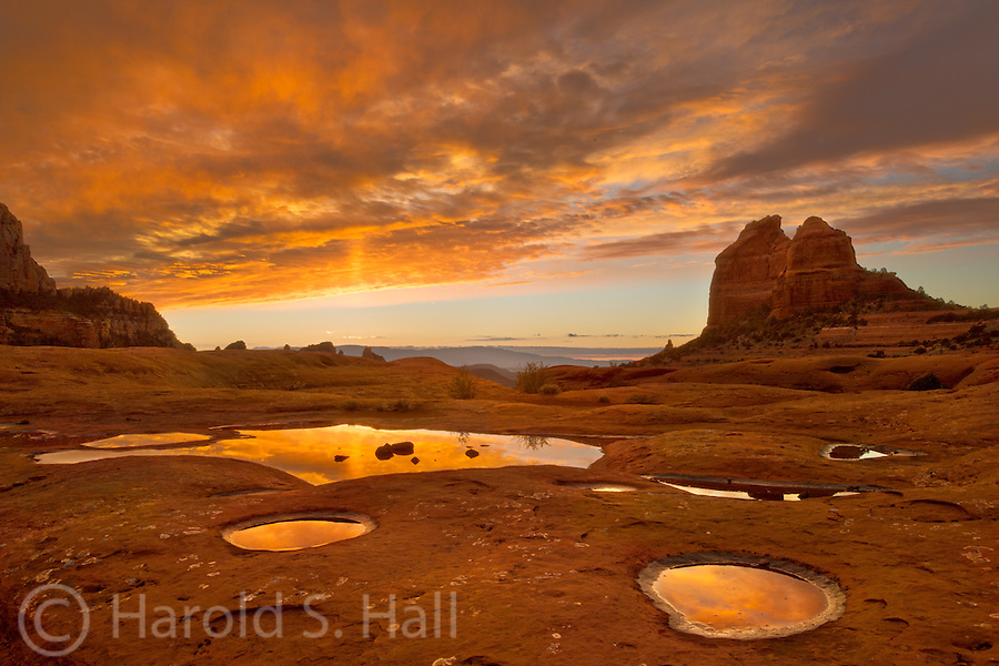 This is an overlook reached by driving on one of the worst 4-wheel drive type roads I have ever conquered.  Large rocks in the road make for a long slow bumpy ride.  If the clouds cooperate, one is rewarded with natures fireworks at sunset.  Recent rains left pools in the famous red sandstone rocks of Sedona, Arizona.