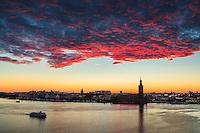 Röda moln över Stadshuset i Stockholm med fartyg på Riddarfjärden