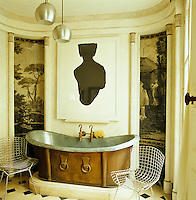 A reclaimed zinc roll-top bath forms the centrepiece of the bathroom and is flanked by a pair of Bertoia chairs and wallpaper panels