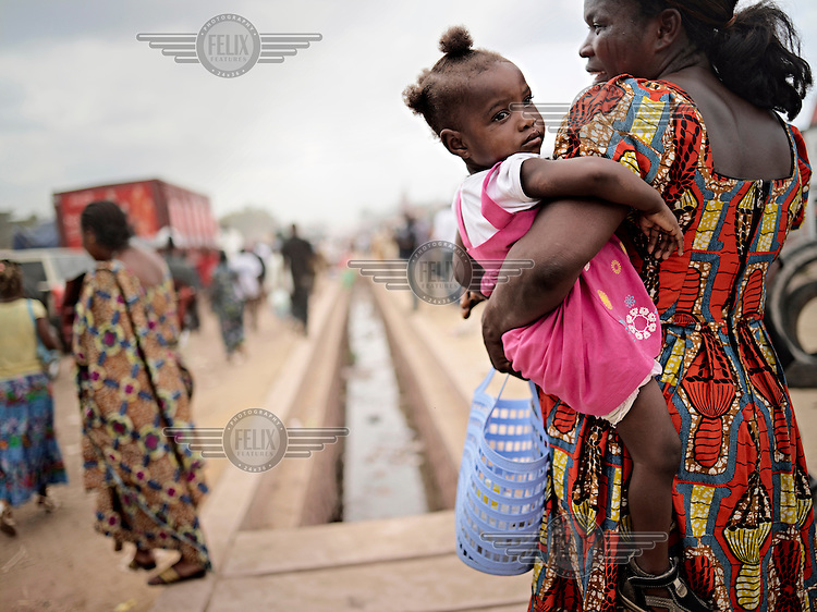 A new road built by China Railway Eight Group is under construction from central Kinshasa to N'Djili international airport. A women is carring her young daughter in the dusty streets.