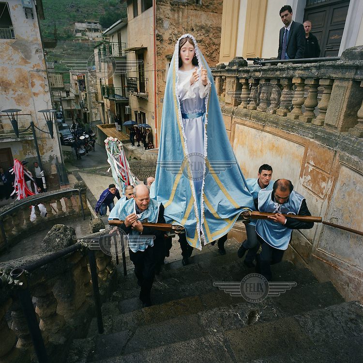 Men carry a statue of the Virgin Mary to the church during the Easter Sunday procession.