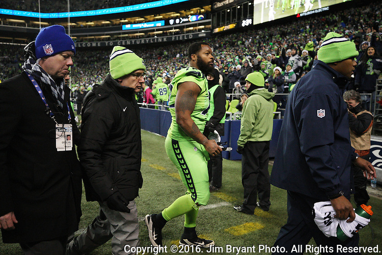 Seattle Seahawks defensive end Michael Bennett (72) is escorted to the team locker room by medical and training staff after being injured tackling Los Angeles Rams running back Todd Gurley at CenturyLink Field in Seattle, Washington on December 15, 2016.  The Seahawks beat the Rams 24-3.  ©2016. Jim Bryant Photo. All Rights Reserved