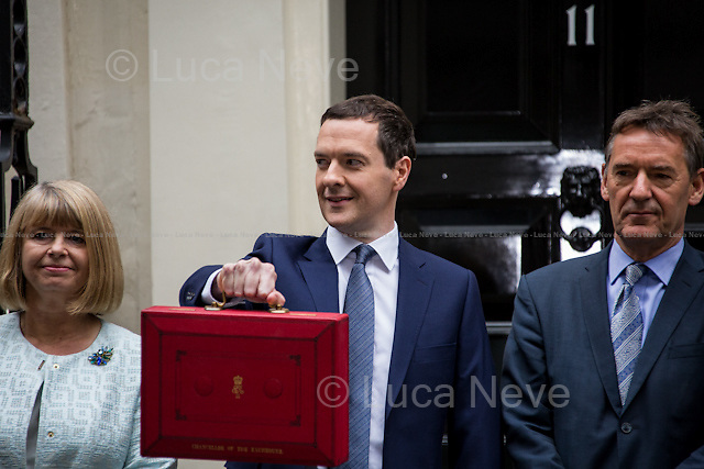 "London, 08/07/2015. UK Chancellor of the Exchequer, George Osborne (followed by his new team) shows the ""red box"" (Budget Box) containing the second Budget for the fiscal year 2015 (the First Budget 2015 was unveiled the 18th of March 2015) and the first since the Conservatives won the election of the 7th of May 2015. This was the first Conservative government Budget since 1996."