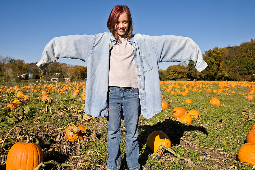 Young female teenager poses as scarecrow on pumpkin farm in the fall