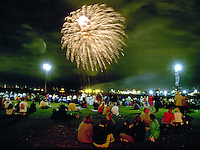 Fireworks illuminate the crowds gathered at a festival.