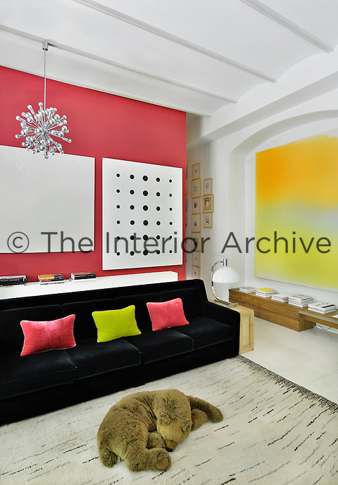 A contemporary living room with barrel ceiling. The room is white with vibrant accent colours. A black sofa provides a strong colour contrast against a coral pink wall.