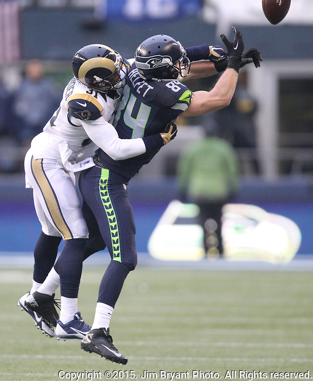 Seattle Seahawks tight end Cooper Helfet (84) is hit by St. Louis Rams safety Maurice Alexander (31) while attending to catch a pass at CenturyLink Field in Seattle, Washington on December 27, 2015.  The Rams beat the Seahawks 23-17.      ©2015. Jim Bryant Photo. All Rights Reserved